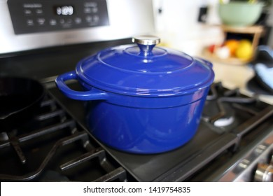 Blue 6 quart Dutch oven resting on a modern natural gas stove.