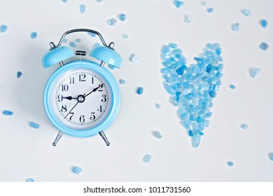 Blue alarm clock and aquamarine stone heart