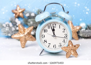 Blue alarm clock,  branches fir tree and golden stars on  blue textured  background. Decorative christmas composition. Selective focus.