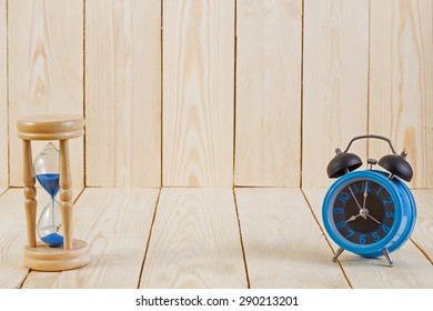 Blue alarm clock and hourglass on wood background.