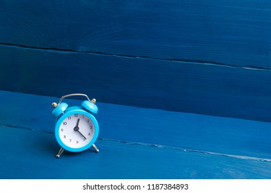 Blue alarm clock on a blue wooden background. The concept of time. Translation of hours for winter or summer time. Punctuality and time planning, business idea. Discipline, minimalism.