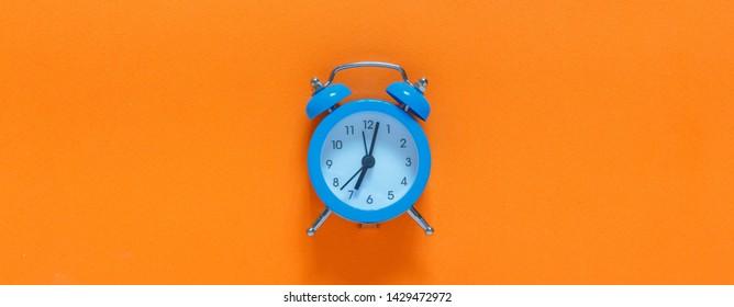 Blue alarm clock, onBlue alarm clock, on an orange background, minimalism an orange background, minimalism