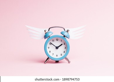 blue alarm clock with origami wing over pink pastel background. valentine romance day concept. greeting card template.