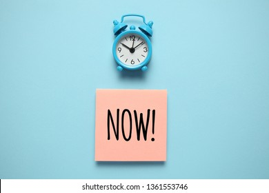 Blue alarm clock and paper reminder, now. Time management, priorities, efficiency, control and goals.