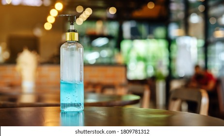 Blue alcohol gel bottle for hand cleaning to prevent the spreading of the Coronavirus (Covid-19), Placed on table to service for customers in the cafe. Healthcare concept. New normal lifestyle