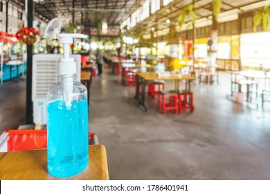 Blue alcohol gel bottle on table for customers to clean their hands before entering the food court to prevent the spread of Corona virus(Covid-19).New normal lifestyle.Trends of supporting business