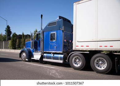 Blue American made model of Big rig semi truck with chrome accessories and pipes and with long fuel tank and high cab section for rest of truck drivers with dry van semi trailer running ahead on road