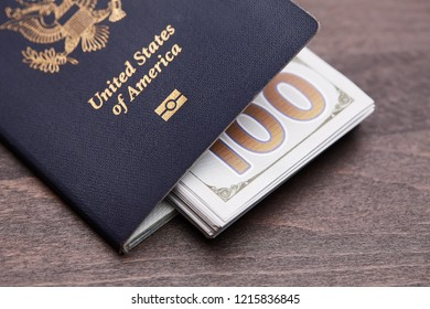 Blue American passport with money on top of a wooden desk. American passport and dollars banknotes. money and travel concept.