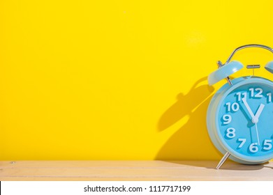 Blue analog alarm clock on the wooden table over yellow background.Alarm clock showing time 1 o'clock.