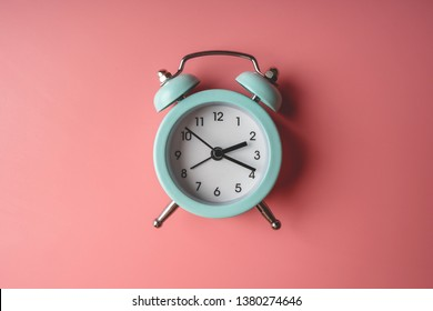 Blue analog metal alarm clock on stylish blue-pink background. The concept of time in pastel colors
