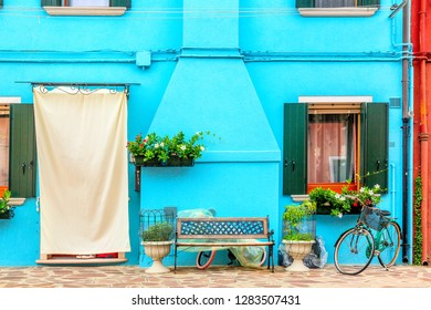 Blue aqua colored house with flowers, bench and a bicycle. Colorful houses in Burano island near Venice, Italy. Venice postcard. Famous place for european tourism and travel.