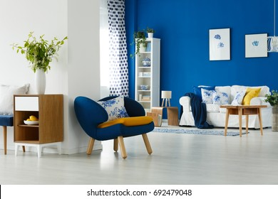 Blue armchair with mustard pillow by the white wall in lounge