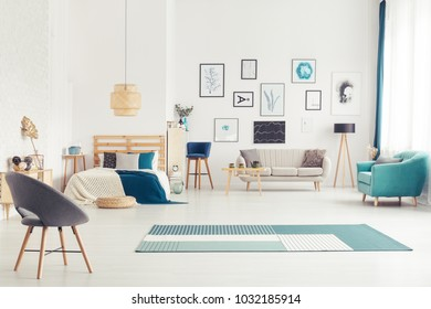 Blue armchair near beige sofa and lamp in cozy open space interior with bed and posters