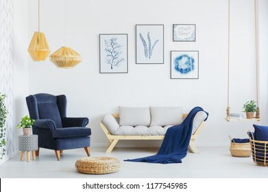 Blue armchair next to a grey sofa, wicker pouf and lamps in a living room interior. Real photo