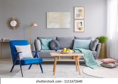 Blue armchair with pillows standing next to wooden table with fresh apples in grey living room interior with decorative mirror and posters hanging on the wall and grey lounge with cushions