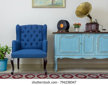 Blue armchair, vintage wooden light blue sideboard, old phonograph (gramophone), vinyl records on beige wall