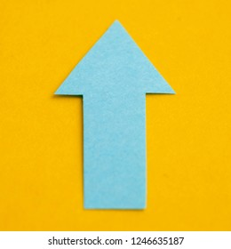 Blue arrow made of paper on a yellow background.