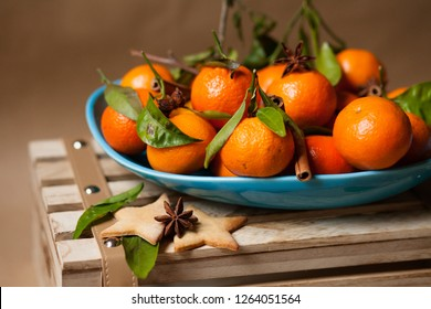 Blue asymmetric bowl with ripe oranges with branches and leaves on a rustic wooden case. Handmade gingerbread biscuits, anise and cinnamon as decor elements. Craft paper as a background