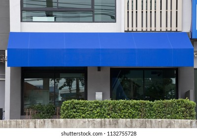 blue awning over glass door of office