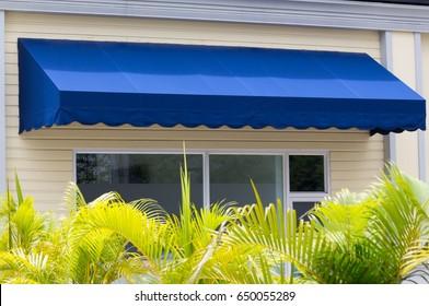 blue awning over white aluminium frame window of shop