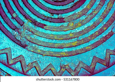 blue azure part of old metal rusty manhole cover with long parallel lines and zigzag in a circle, rainbow picture on metal manhole with recess and rusty parts