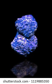 Blue Azurite mineral gemstone in front of black background, rough crystal with reflection