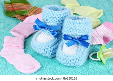 Blue baby booties, socks and pacifier on blue background