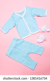 Blue baby clothes on pink background with shirt, trousers and white socks on pink background. Child design summer fashion. Flat lay. Top view