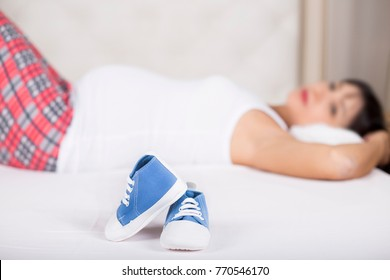 Blue baby shoes on pregnant belly. Pregnancy, love, maternity and expectation concept. Pregnant woman expecting baby.