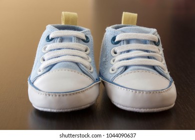Blue baby sneakers on a wooden surface