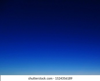 blue background. The clear sky during sunrise in the morning. no cloud in the sky and the the sky is deep blue to light blue and light yellow