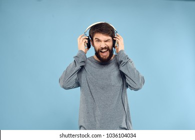 blue background, handsome man with headphones, emotions