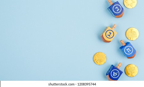 Blue background with multicolor dreidels and chocolate coins. Hanukkah and judaic holiday concept. Horizontal, wide screen banner format