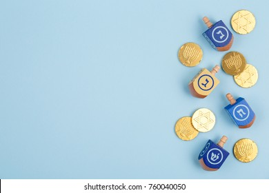 Blue background with multicolor dreidels and chocolate coins. Hanukkah and judaic holiday concept. Horizontal