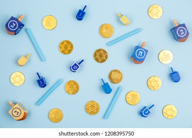 Blue background with multicolor dreidels, menora candles and chocolate coins. Hanukkah and judaic holiday concept. Horizontal