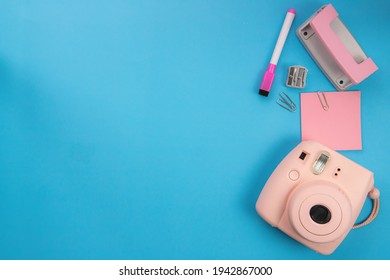 Blue background Pink polaroid camera, pink magic pen and post-it.