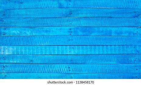 Blue background. A blue rough wooden desk.