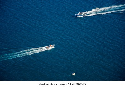 A blue background with three tourist boats traveling in the sea in opposite directions