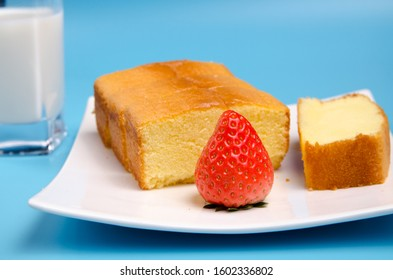 Blue background and white milk in glass, cake in white plate
