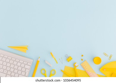 Blue background and yellow school supplies. Flat lay.