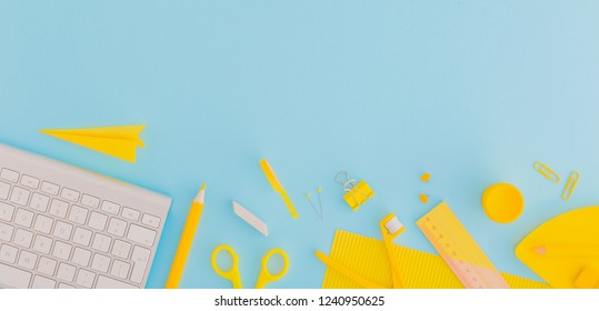 Blue background and yellow school supplies. Back to school. Flat lay.