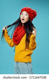Blue background yellow sweater red hat woman scarf