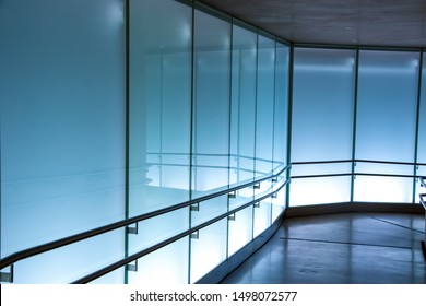 Blue backlit tempered glass with stainless steel railings, along a cement floored hallway.