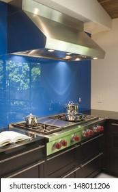 Blue backsplash and stainless steel vent hood in modern kitchen