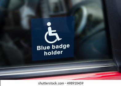 Blue Badge Holder sign. White and blue sticker with a wheel chair symbol on stuck to the inside of a car window.