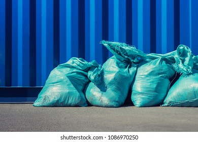 Blue bags with building trash arraged next to blue wall. Disposal of constration rubbish.