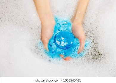 Blue ball of bath salts. Bath salt ball dissolves in the hands. Bomb. Foam.