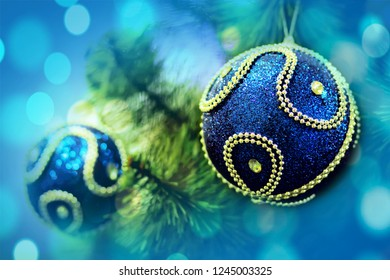 Blue ball ornament hanging on the pine leaf for decoration christmas tree with blur colorful light.