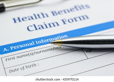 Blue ballpoint pen and a health benefits claim form on a clipboard. A blank / empty form is waiting to be filled and signed by patient / insured person.