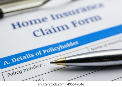 Blue ballpoint pen and a home insurance claim form on a clip board. A blank / empty form is waiting to be filled and signed by a policyholder / insured person.